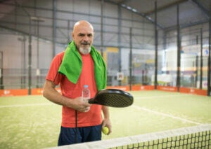 A man standing on a padel tennis court.