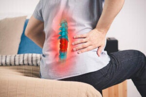 A person sitting down with back pain.