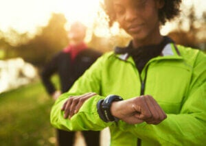 A woman on a run checking her fitness watch.