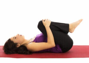 A woman stretching on the floor.