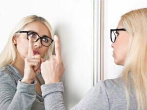 A woman talking to herself in the mirror.