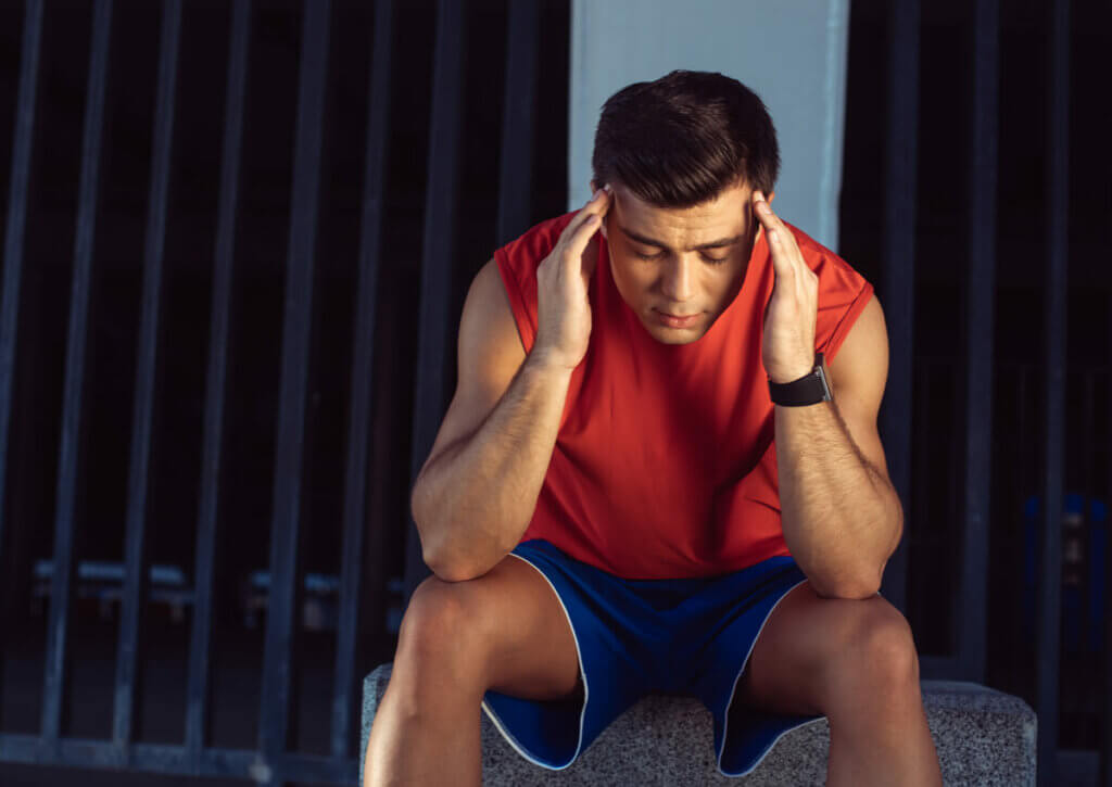 Athlete sitting with head in hands, looking stressed