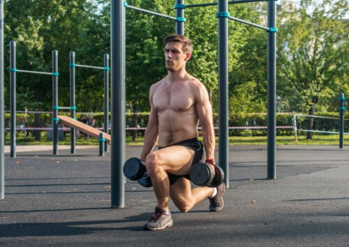 A man doing common dumbbell lunges outdoors.