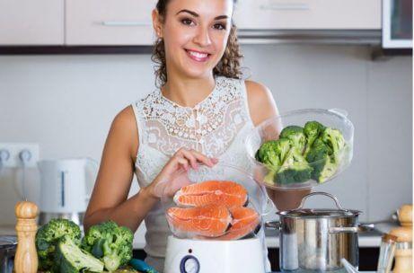 A girl preparing fresh fish and broccoli