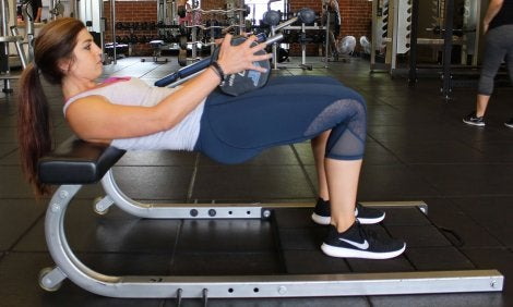 Woman on a bench lifting weights.