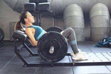 Women lifting weights on a bar.