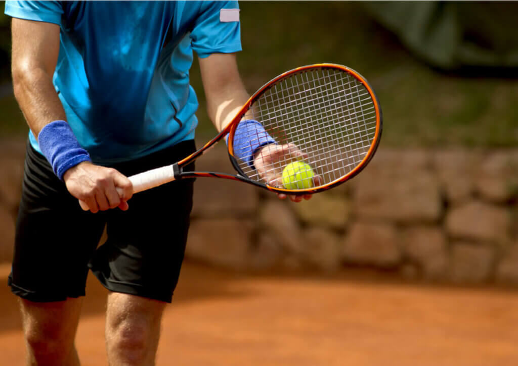 tennis player preparing to serve; paddle tennis and tennis