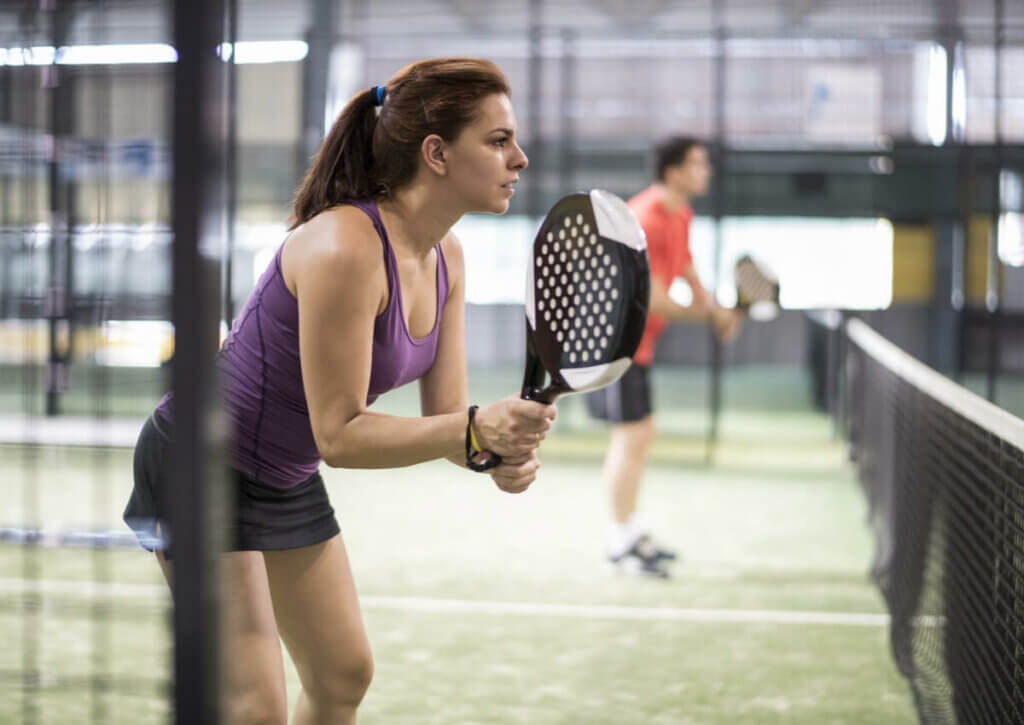 woman playing paddle tennis about to serve the ball; paddle tennis and tennis