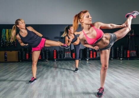 Women doing high kicks in a fitness center