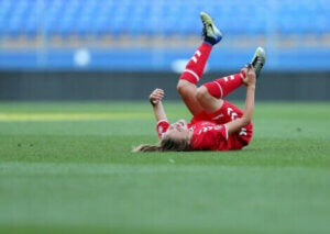 A soccer player suffering an injury on the field.