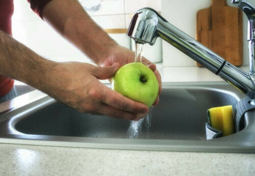 A person washing a green apple.