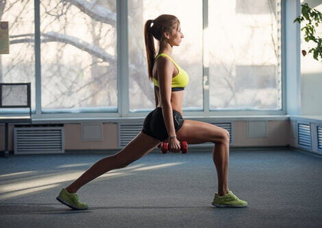 A woman doing lunges with hand weights.