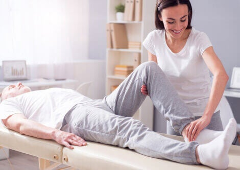 A physiotherapist helps a patient to stretch his knee.