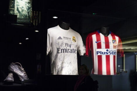 Two soccer jerseys on mannequins.