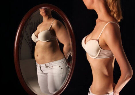 A woman looks in a mirror and sees a distorted image of herself.