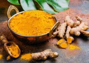 A bowl of turmeric next to some turmeric root.