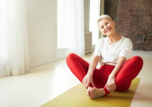 A woman smiling while doing yoga.