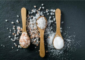 Three wooden spoons containing mineral salts, which are one of the causes of fluid retention.