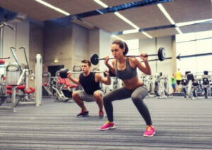 Two people squatting in the gym.