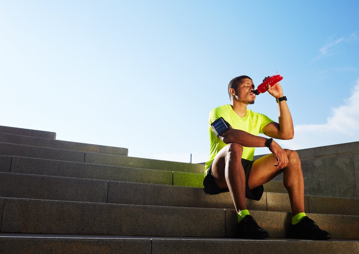 A man drinking a sports drink.
