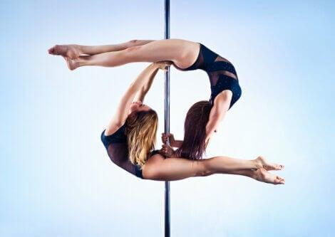 Two women doing pole dance.