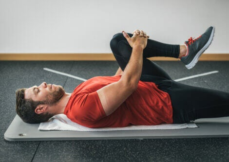 A man lying down doing glutes stretches.