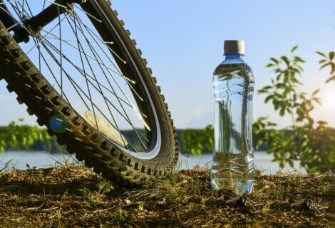 A bottle of water sitting next to a bicycle.