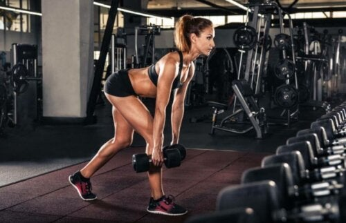 A woman lifting weights at the gym.