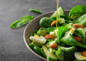 A bowl of green leafy vegetables which contain vitamin K.