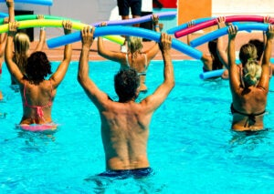A group of people performing water aerobics.