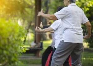 A group performing Chi Kung practice outside.