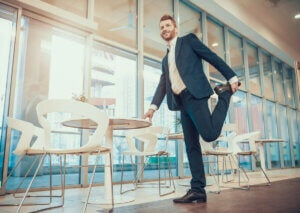 A man in a suit stretching his quadriceps.