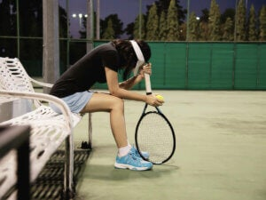 A tennis player sitting down in thought.