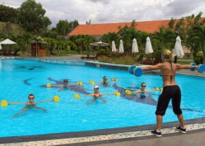 A woman leading a water aerobics session.