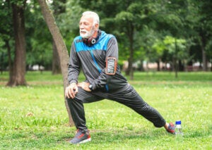 An older man stretching in the park.
