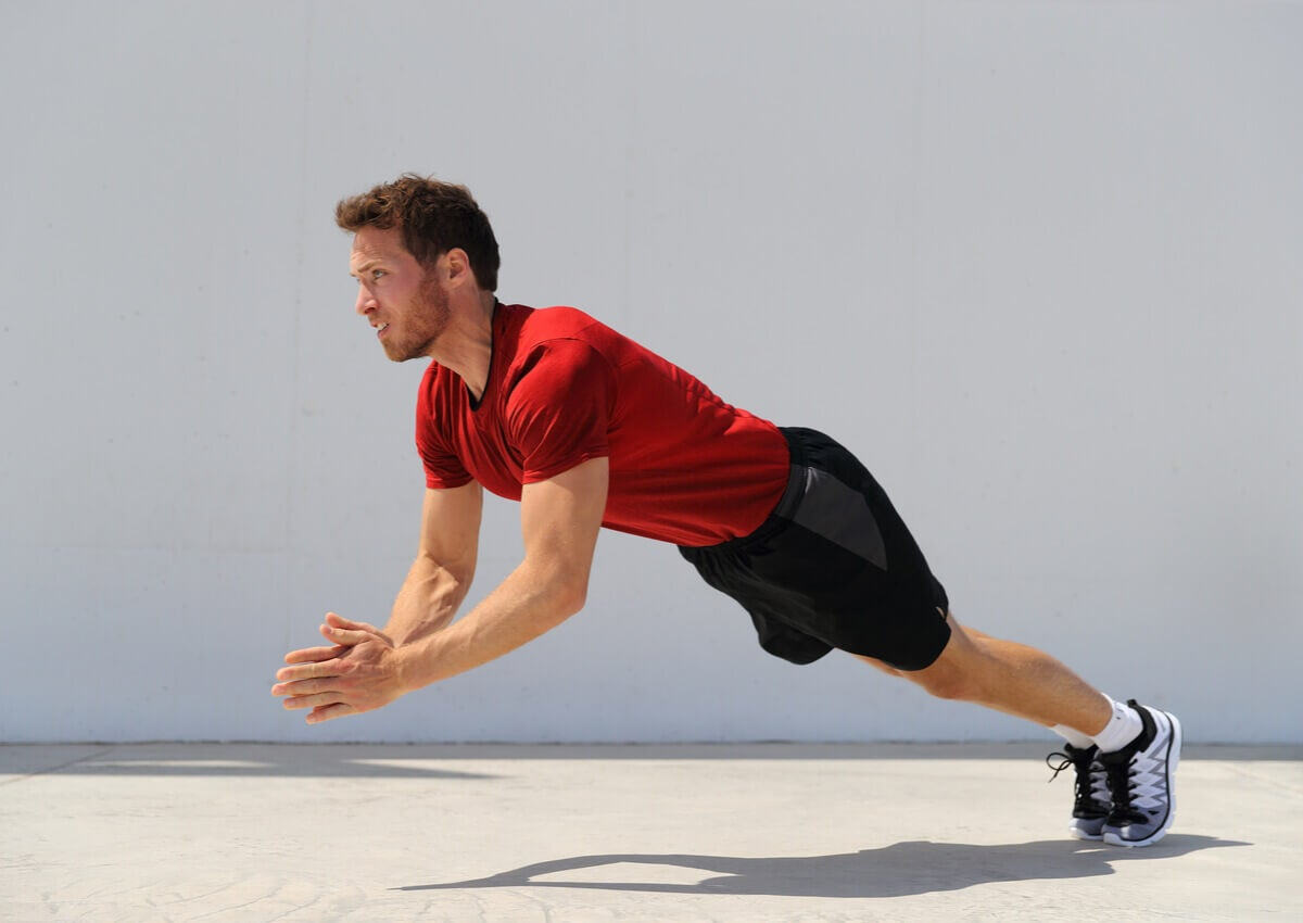 A man doing a clapping push-up.