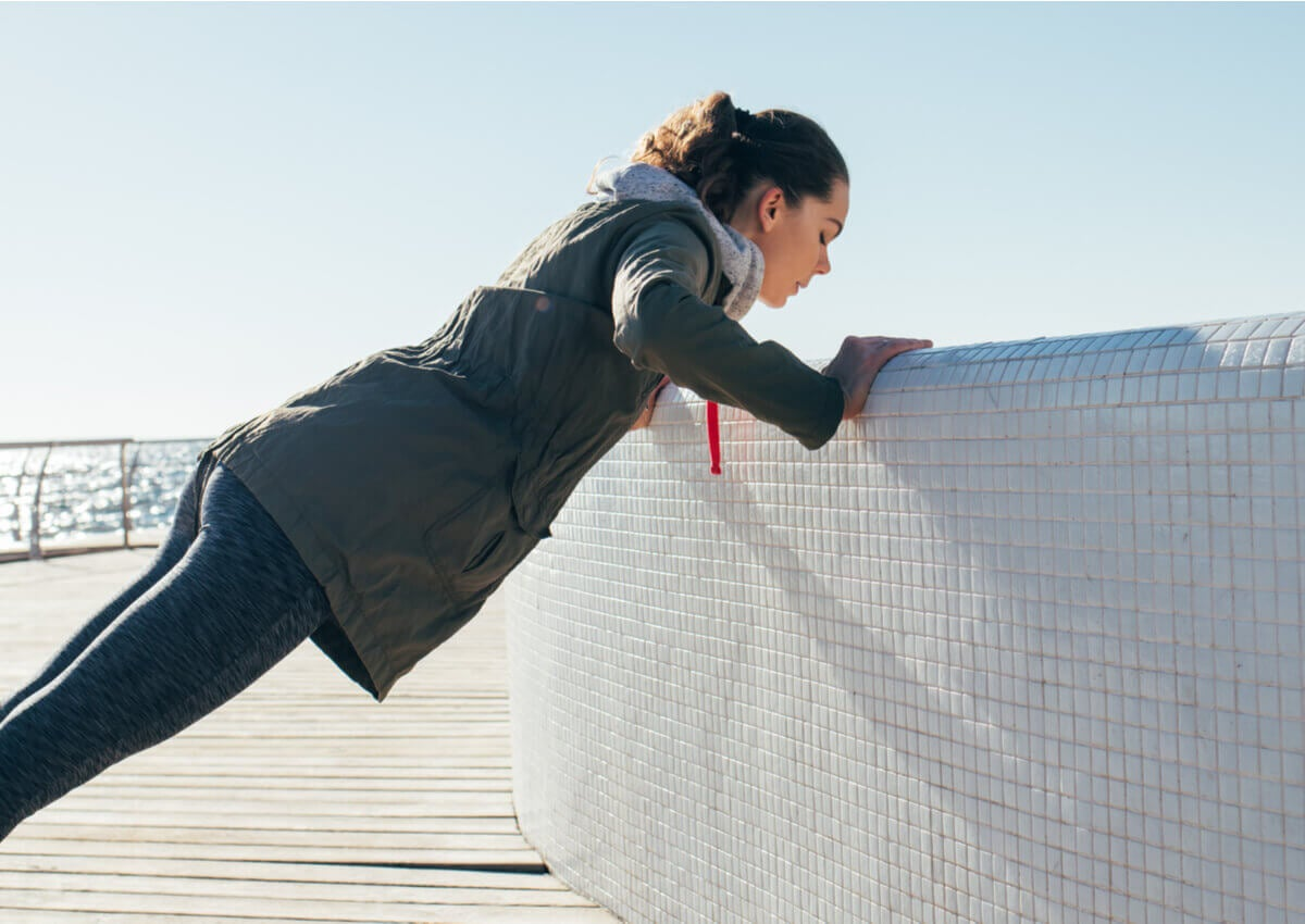 A woman doing a wall push-up.