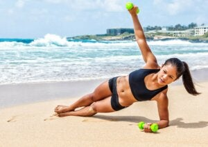 A woman exercisingo with weights on the beach.