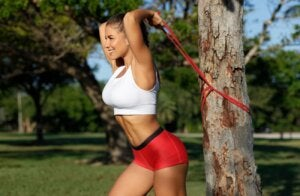 A woman performing an overhead tricep extension against a tree.
