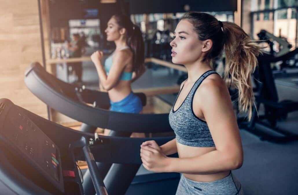 Two women running on treadmills in a gym.