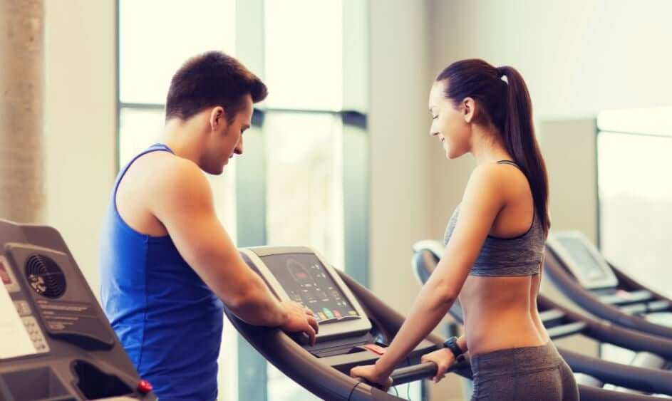 A personal trainer setting up a treadmill for a woman.