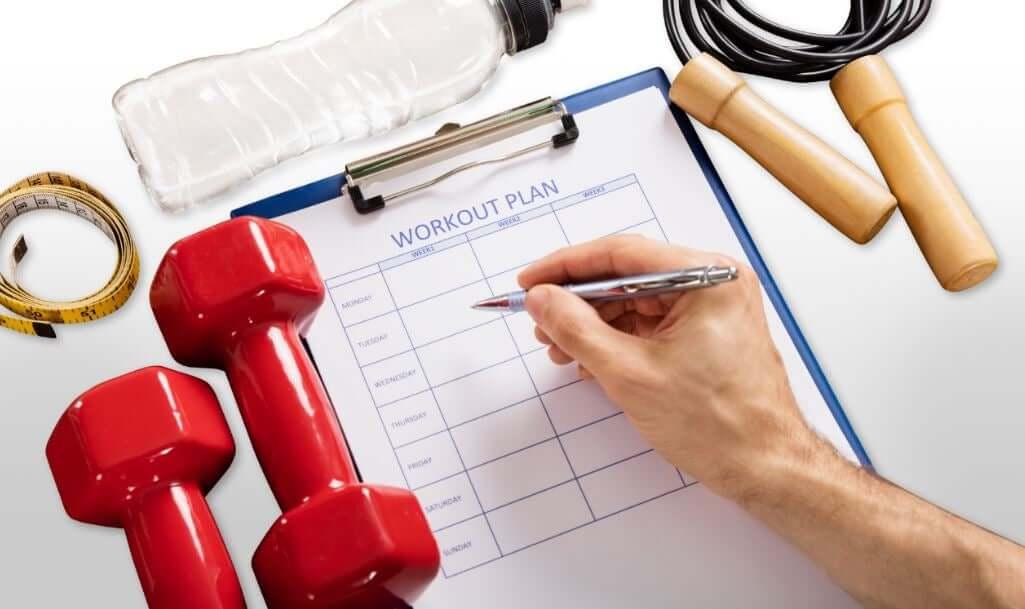 A person creating a workout plan on a calendar.
