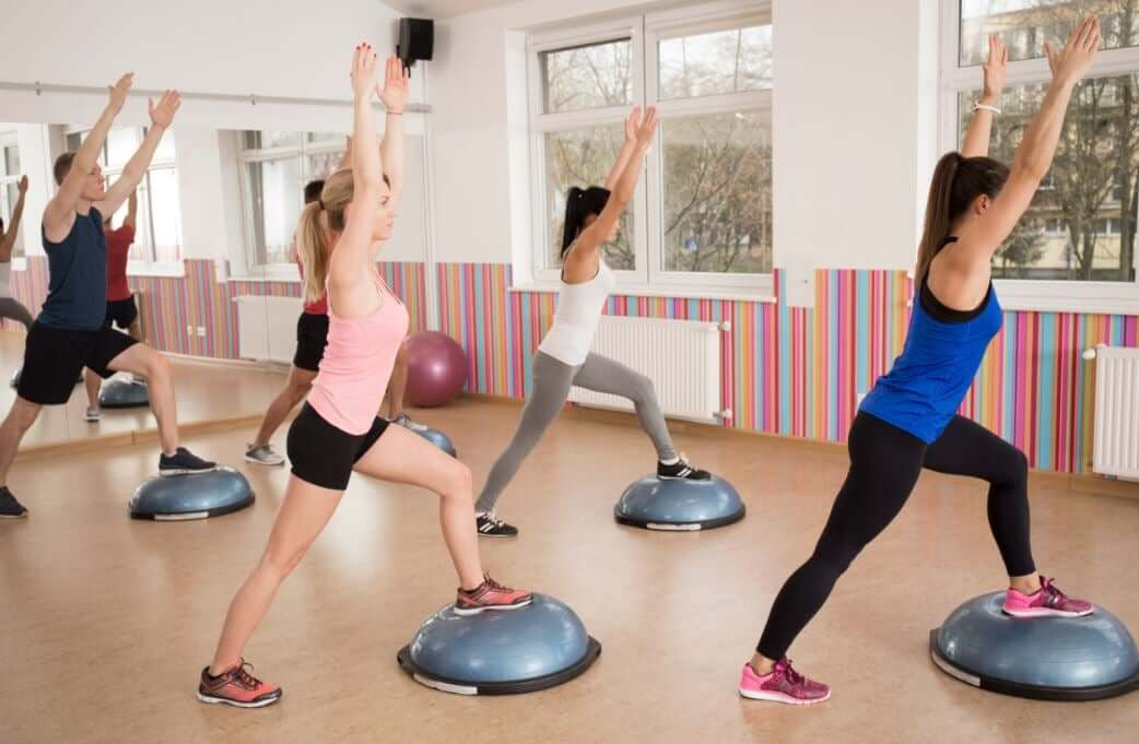 Women in a gym class using the BOSU ball.