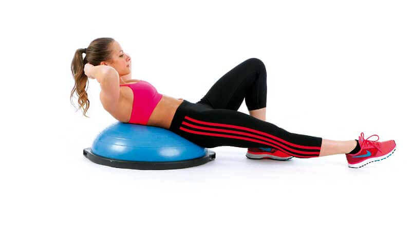 A woman doing situps on a BOSU.