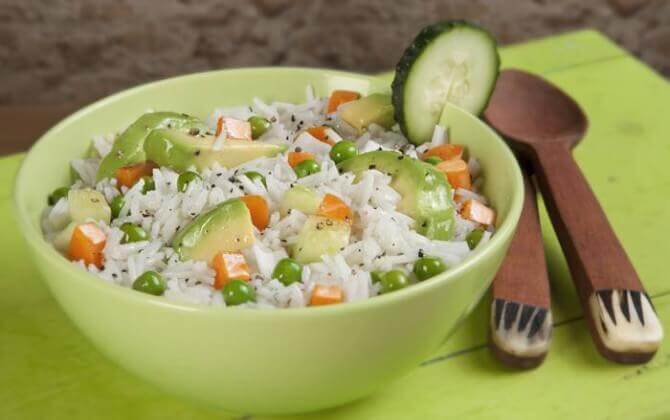 A cold rice salad with peas, carrots, and avocado.