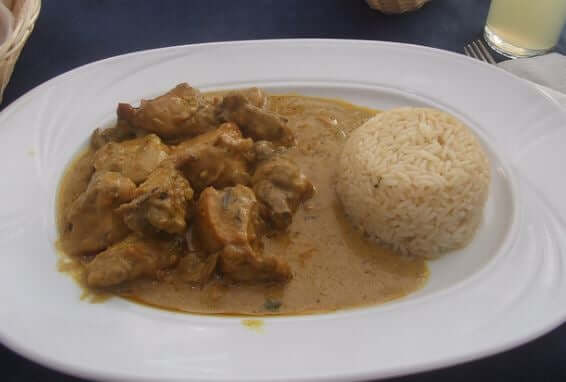 A plate of chicken curry and rice.