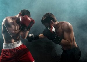 Two people boxing correctly to prevent injuries in this contact sport.