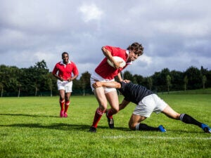 Two players in a rugby tackle.