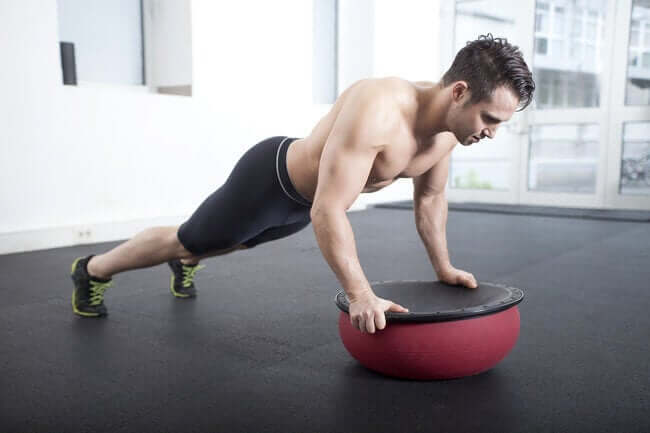 A man doing pushups on a BOSU ball.