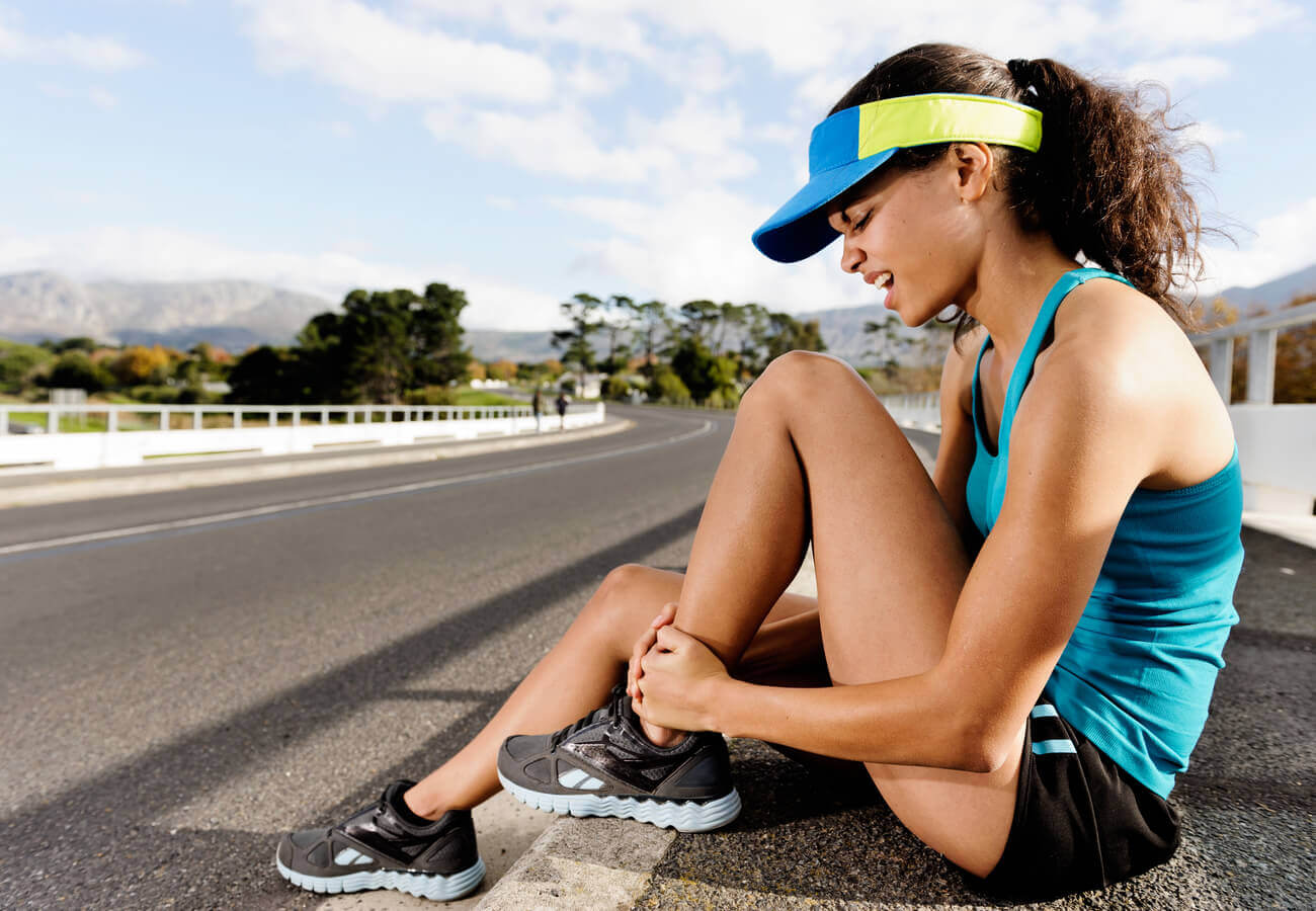 A female marathon runner sitting on the side of the road holding onto her ankle.